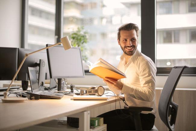 本を手に、微笑む男性